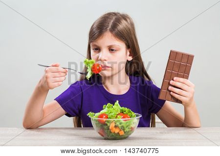 Little girl is unhappy because she does not like to eat salad. She prefers chocolate.