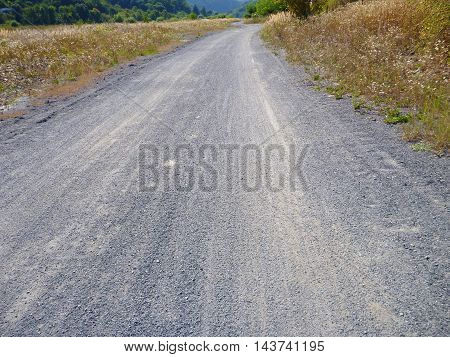 Empty Dirt Gravel Road With Dry Grass