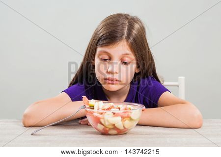 Little girl does not like to eat fruit salad.