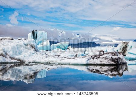 Icebergs and ice floes are reflected in the mirrored water of the ocean Bay. Ice lagoon in July. Summer vacation in Iceland