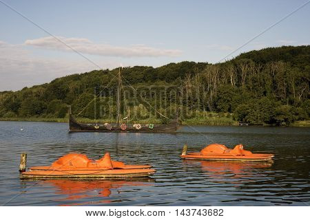 FAARUP VEJLE DENMARK - AUGUST 22 2016: Replica of Viking Ship - Jellingorm and colorful pedalos docked in Faarup Lake Denmark. August 22 2016.