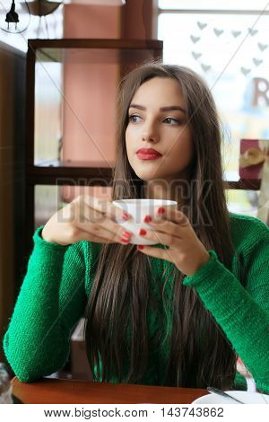 Thoughtful beautiful young woman with long hair drinking tea in cafe