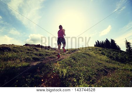 healthy lifestyle young woman trail runner running on beautiful mountain trail