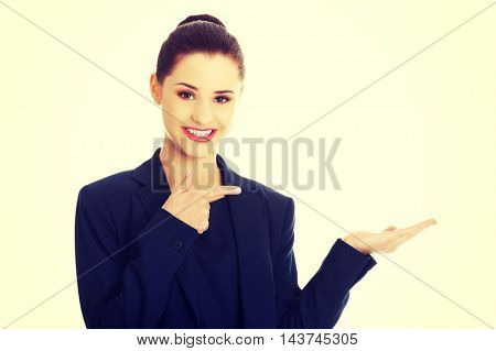 Business woman showing something or copyspase