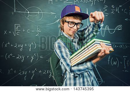 Education, high school, college. Portrait of a student boy standing by a school blackboard.