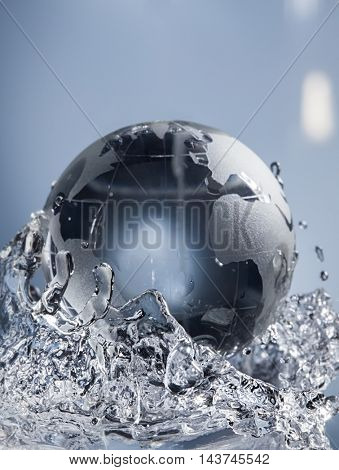 glass globe planet in drop water splash on blue background