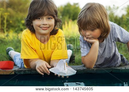 Two boys allowed paper boats from the pier of the river