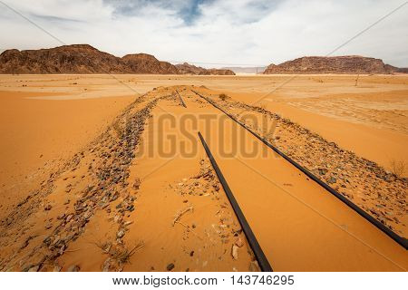 Sand dunes under dramatic sky with backfilled of sand railroad Wadi Rum Jordan. concept of global warming.