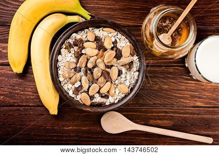 Healthy muesli breakfast with huts and raisins milk banana and honey.