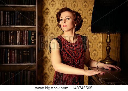 Portrait of a beautiful mature woman in evening dress standing in a room with classic style interior.