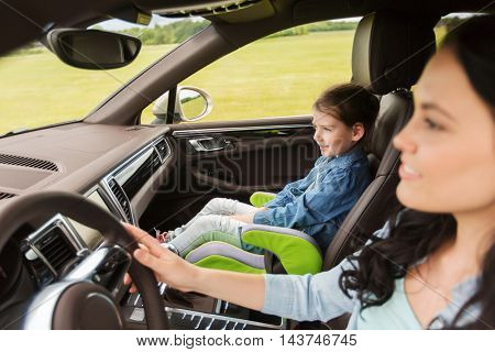 family, transport, road trip and people concept - happy woman with little girl driving in car