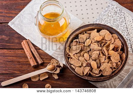 oat flakes and honey on rustic background. granola and musli for breakfast on wooden table.