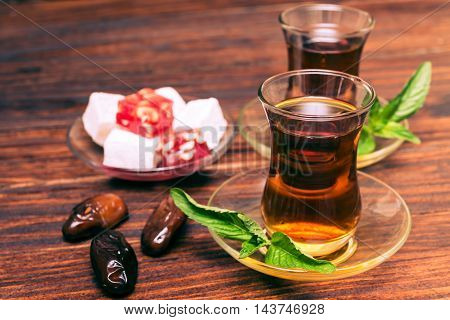 Arabic black tea and dates and sweets on the wooden table.