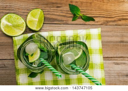 Glasses with mojito and ice on wooden background. Mojito ingredients - lime mint rum ice top view