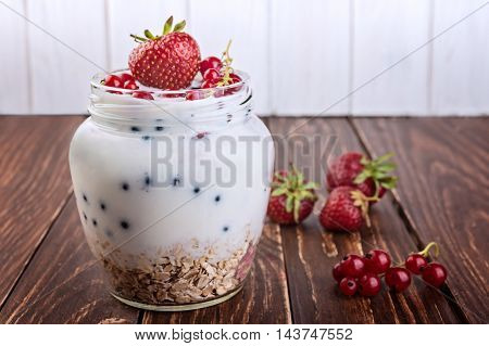 Yogurt dessert with muesli and fresh red currant and strawberry on wooden table