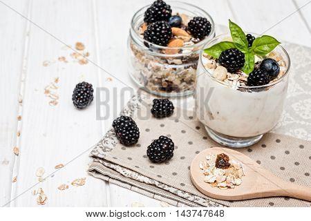 homemade yogurt with muesli amd berries on wooden background