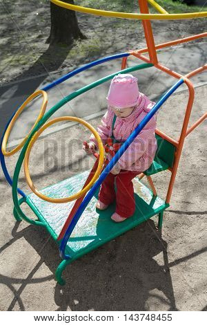 Little girl is playing handling game monkey bar helicopter on outdoor playground