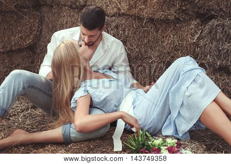 Loving couple kissing in the hay in the village.