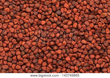 Organic dry Annatto (Bixa orellana) seeds. Macro close up background texture. Top view.