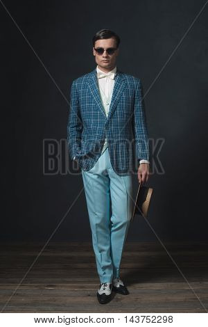 Vintage 1920S Business Man Wearing Blue Checkered Jacket And Sunglasses. Holding Straw Hat.