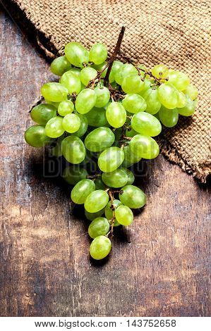 Grapes on a wooden table close up rustic vintage style with copy space. Fresh grapes on wood. Autumn fruit top view
