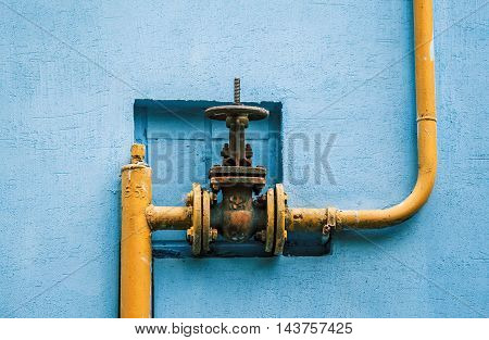 yellow gas pipe with a valve on the blue wall of a building