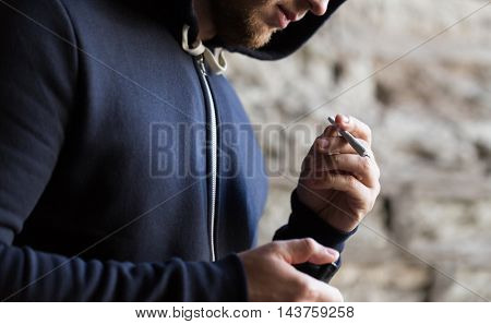 drug use, substance abuse, addiction, people and smoking concept - close up of addict with marijuana joint and lighter