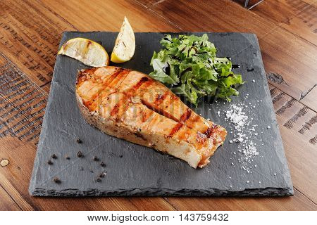 trout fish steak with lemon on a shale surface. wooden background