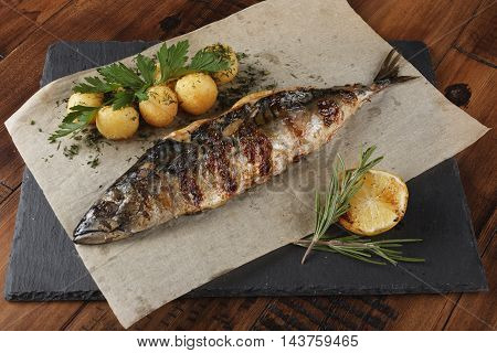 Mackerel fish fried with young potato on shale surface. wooden background