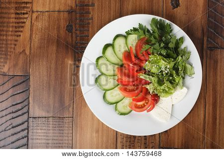 vegetable mix (salad, cucumber, tomato, parsley) and chees on a white plate. wooden background.