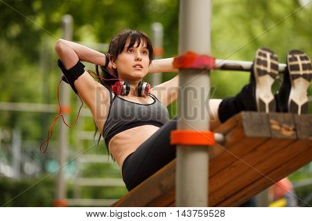 Brunette woman in workout clothes doing sports in park on summer day
