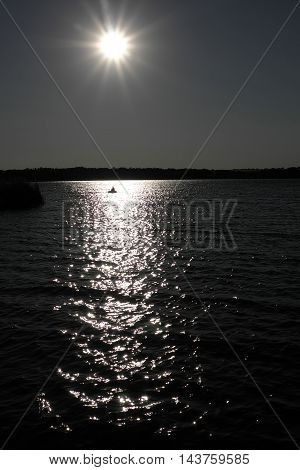 Sunset lake sparkling. fisherman driving a small fishing boat in fishing.