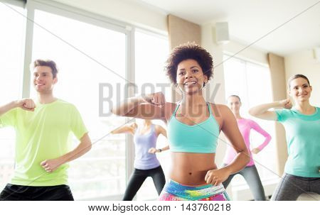 fitness, sport, exercising and training concept - group of smiling people with coach dancing or working out fighting stance in gym