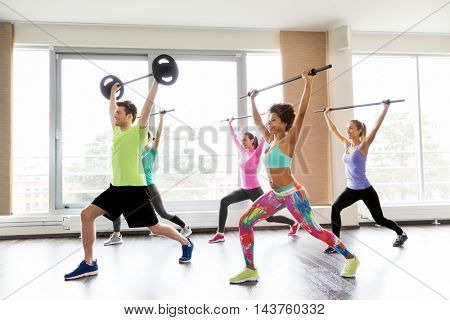 fitness, sport, training, exercising and lifestyle concept - group of people with barbell bars doing lunge in gym