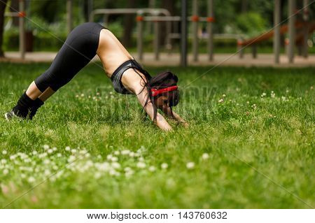 Flexible athletic young woman with headphones doing stretching on grass next to outdoor training gym