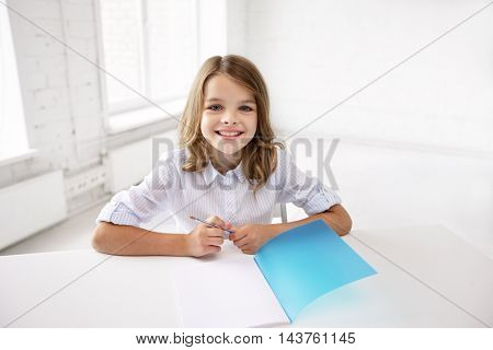 education, elementary school, learning and people concept - happy smiling girl with notebook and pen