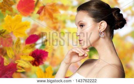 beauty, jewelry, accessories, people and luxury concept - close up of beautiful asian woman face with earring over autumn leaves background