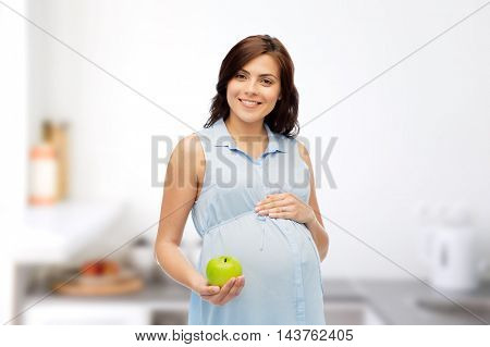 pregnancy, healthy eating, food and people concept - happy pregnant woman holding green apple over kitchen background