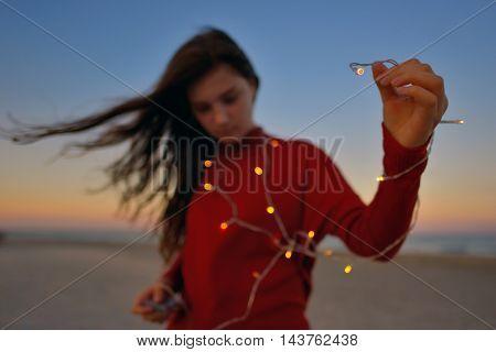 Teen girl with lights on beach