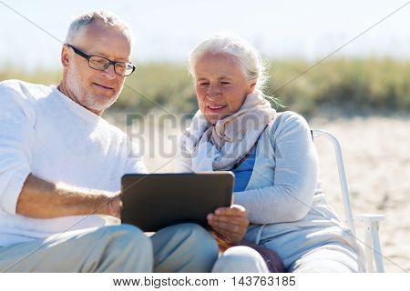family, age, travel, tourism and people concept - happy senior couple with tablet pc computer sitting on deck chairs on summer beach