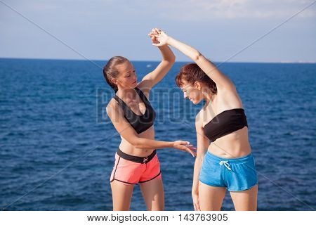 fitness trainer helps the girl to do the exercises