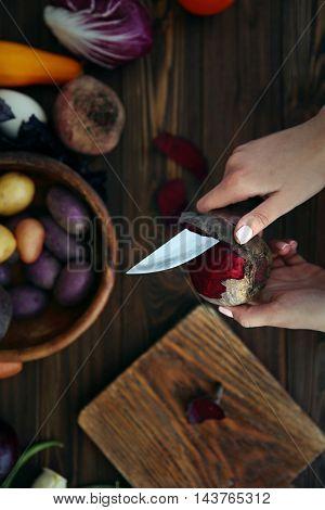 Woman peeling beetroot on kitchen, top view