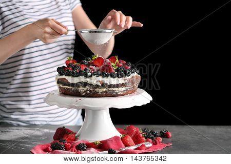 Woman decorating sweet fruitcake with powdered sugar