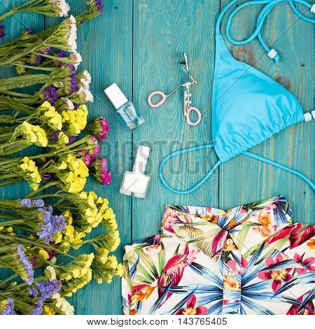 Dress, Swimsuit, Cosmetics Makeup, Bijou And Essentials On Blue Wooden Background
