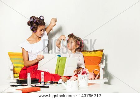 Little girl playing with her mother and looking at a photo album on white