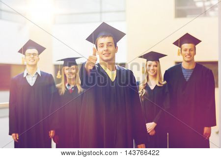 education, graduation, gesture and people concept - group of smiling students in mortarboards and gowns showing thumbs up outdoors