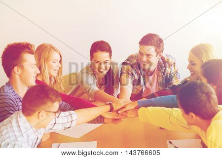 education, teamwork and people concept - smiling students with papers putting hands on top of each other