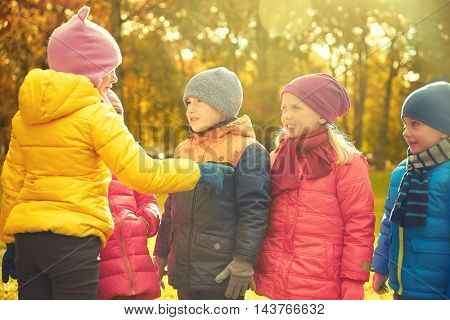 childhood, leisure, friendship and people concept - group of happy kids in autumn park counting and choosing game leader