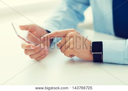 business, technology and people concept - close up of male hand holding and showing transparent smart phone and watch at office
