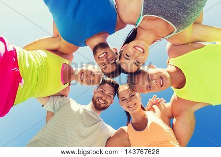 fitness, sport, friendship and healthy lifestyle concept - group of happy teenage friends in circle outdoors